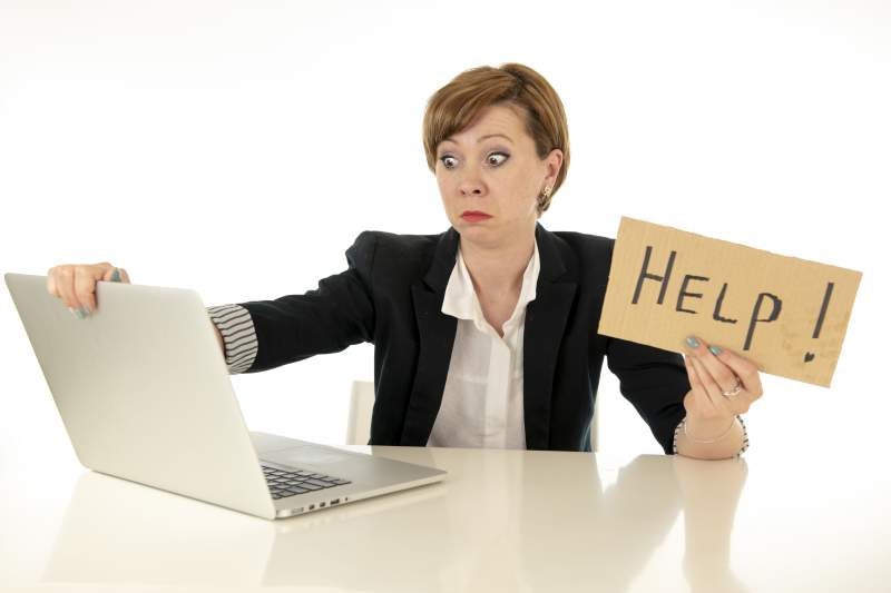 Photo of young red haired caucasian tired and frustrated business woman working on her computer holding a help sign at work office desk on a white background.